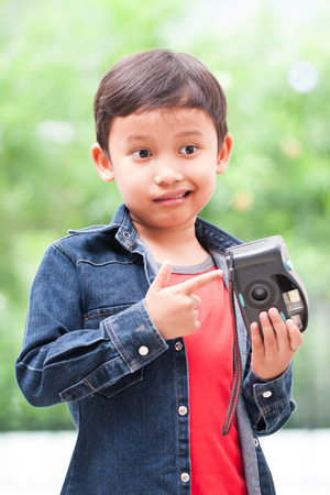 compact camera: Happy asian boy with compact camera.