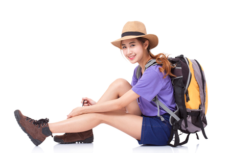 knapsacks: Woman traveler sitting on the floor with backpack on white background Stock Photo