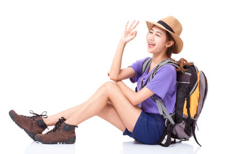 knapsacks: Woman traveler sitting on the floor and showing ok signwith backpack on white background