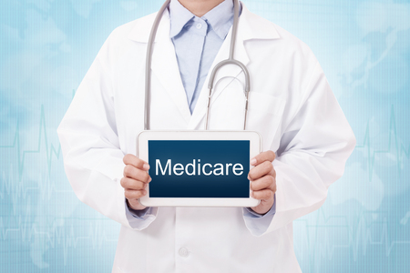 medicare: Doctor holding a tablet pc with medicare text on blue background Stock Photo