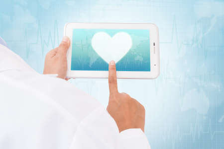 doctor tablet: Doctor hand touch screen heart symbol on a tablet. medical icon Stock Photo