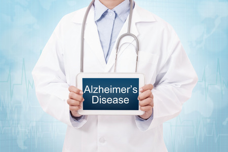brain aging: Doctor holding a tablet pc with alzheimers disease sign on blue background
