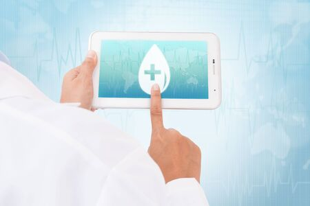 doctor tablet: Doctor hand touch screen Donate blood Blood Drop symbol on a tablet. medical icon