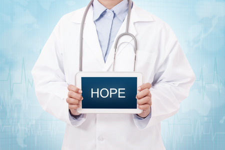 Doctor holding a tablet pc with hope sign on the display Stock Photo