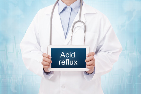 acid reflux: Doctor holding a tablet pc with acid reflux sign on blue background