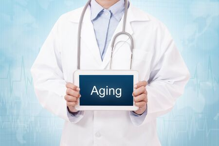 geriatrics: Doctor holding a tablet pc with aging sign on blue background Stock Photo