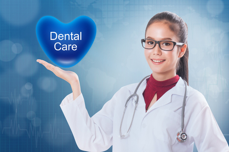 dentalcare: Female doctor holding heart with dental care sign on medical background. Stock Photo