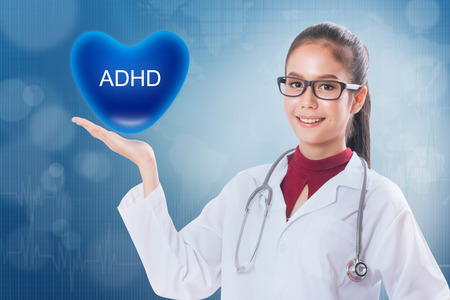 inattention: Female doctor holding heart with ADHD sign on medical background.