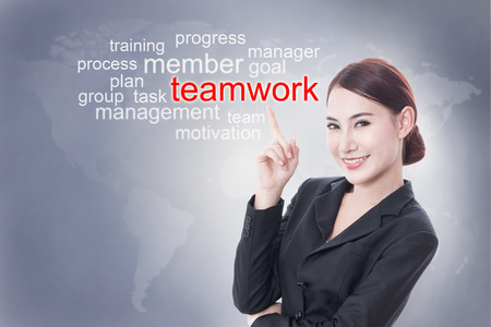 teaming: Businesswoman pointing at teamwork word on screen. business concept.