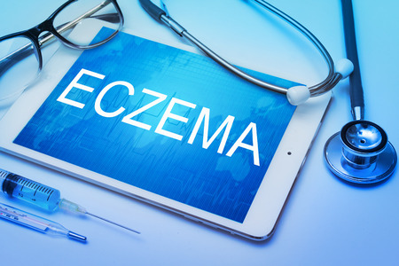 eczema: eczema word on tablet screen with medical equipment on background Stock Photo