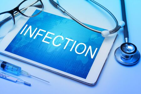 medico: Infection word on tablet screen with medical equipment on background