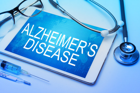insanity: Alzheimers Disease word on tablet screen with medical equipment on background