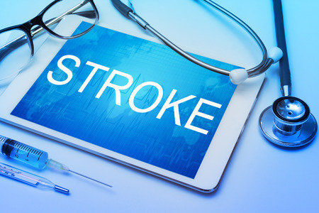 sudden death: Stroke word on tablet screen with medical equipment on background Stock Photo