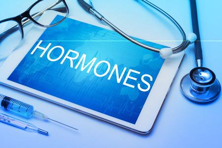 hormonas: Hormonas palabra en la pantalla de la tableta con el equipo m�dico en el fondo