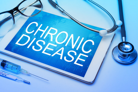 malady: Chronic Disease word on tablet screen with medical equipment on background Stock Photo