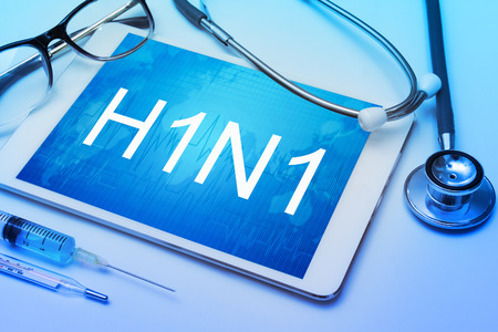 swine flu vaccines: H1N1 word on tablet screen with medical equipment on background