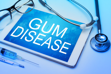 Periodontitis: Gum disease word on tablet screen with medical equipment on background Stock Photo
