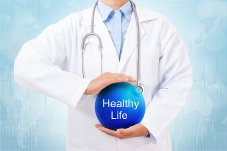overeat: Doctor holding blue crystal ball with Healthy Life sign on medical background.
