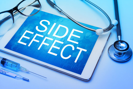 adverse reaction: Side Effect word on tablet screen with medical equipment on background