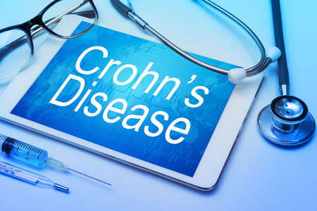 s stomach: Crohns disease word on tablet screen with medical equipment on background