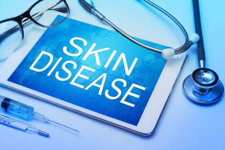 skin disease: Skin Disease word on tablet screen with medical equipment on background