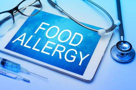 hypersensitivity: Food allergy word on tablet screen with medical equipment on background