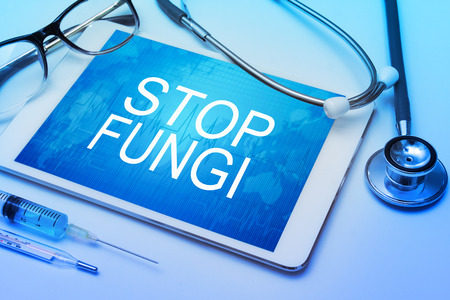 fungal disease: Stop fungi word on tablet screen with medical equipment on background