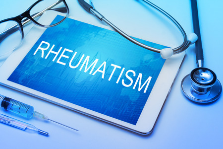 rheumatism: Stop rheumatism word on tablet screen with medical equipment on background.