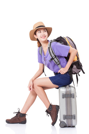 Woman traveler sitting on suitcase with backpack on white background