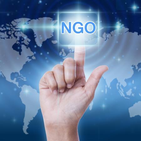 hand pressing NGO (Non-Governmental Organization) sign on virtual screen. business concept