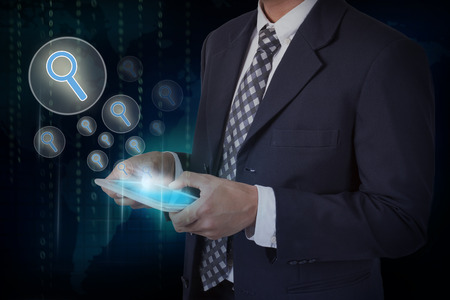 Businessman hand touch search icons on a tablet