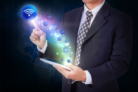 both: Businessman holding tablet with pressing wifi sign icon button. internet and networking concept