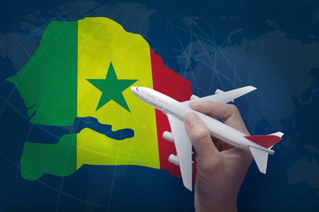 hand holding airplane with map of Senegal.