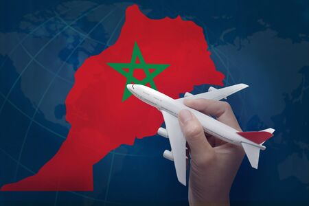 hand holding airplane with map of Morocco.