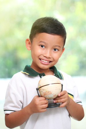 Little boy is holding a globe on green background