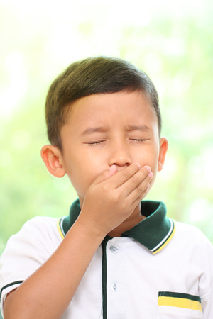 A Little boy coughing on green background