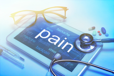 Pain word on tablet screen with medical equipment on background