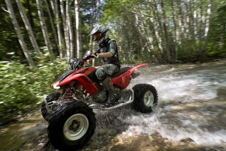 Teen aged girl riding quad through creek in the forest.