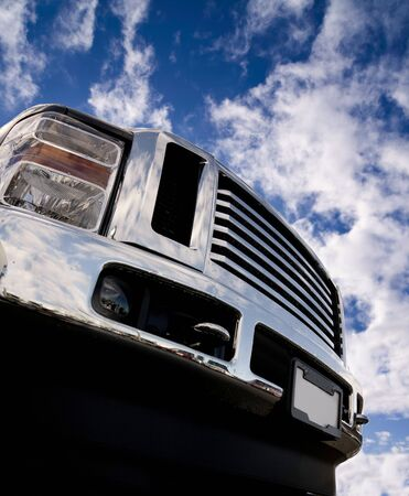 chrome: Close-up of the front of a shiny Truck. Lots of chrome. Low angle looking up towards blue sky with partial clouds.