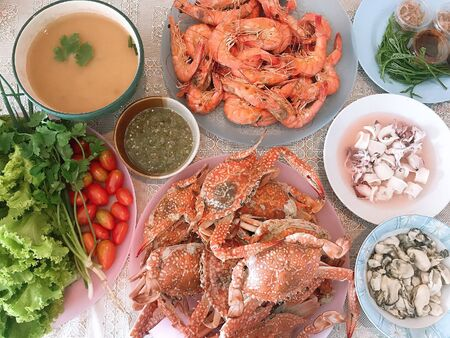 Dinner is seafood. There are shrimp, crab, squid, clam, tomato, salad and soup.