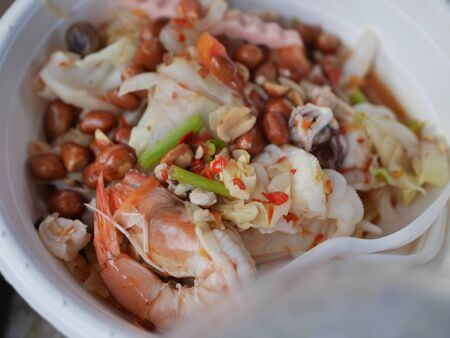 Spicy seafood salad. Thai food has shrimp, squid, onion on a white plate