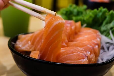 Sasimi Chopsticks, salmon, on a black cup, close up, green background Foto de archivo - 135517225