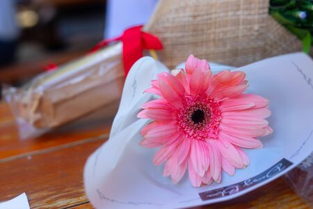 Pink bouquet of flowers placed on a brown wooden table Foto de archivo - 135517145