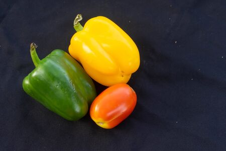 Yellow and green bell peppers with red tomatoes On a black background Foto de archivo - 137599789