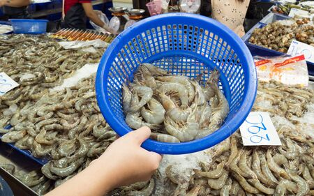 A womans hand was carrying a basket of blue prawns that he had picked up nearby. Stock fotó