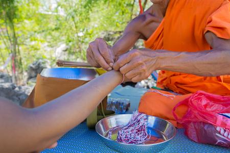 Ein Mönch band heiligen Faden am Handgelenk des Reisenden. Wat Wat Tham Tempel, Thailand Standard-Bild