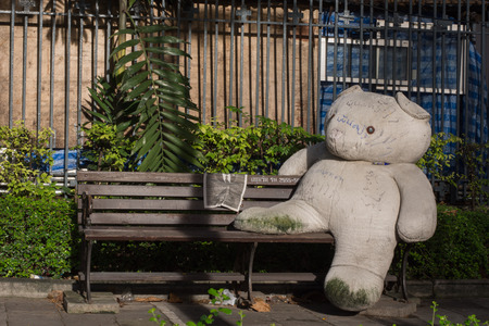 seating: Big teddy bear sit on the public seating Stock Photo