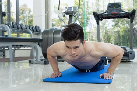 fitness hombre guapo ejercicio haciendo flexiones como parte del entrenamiento culturismo en el gimnasio o gimnasio, deporte y concepto de la salud.