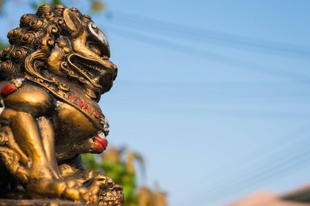 asian art: Singha statue or lion statue on blue sky background and copy space for text Stock Photo
