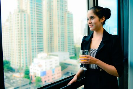 smile of beautiful business woman at the window with champagne, business successful concept, vintage style Stock Photo
